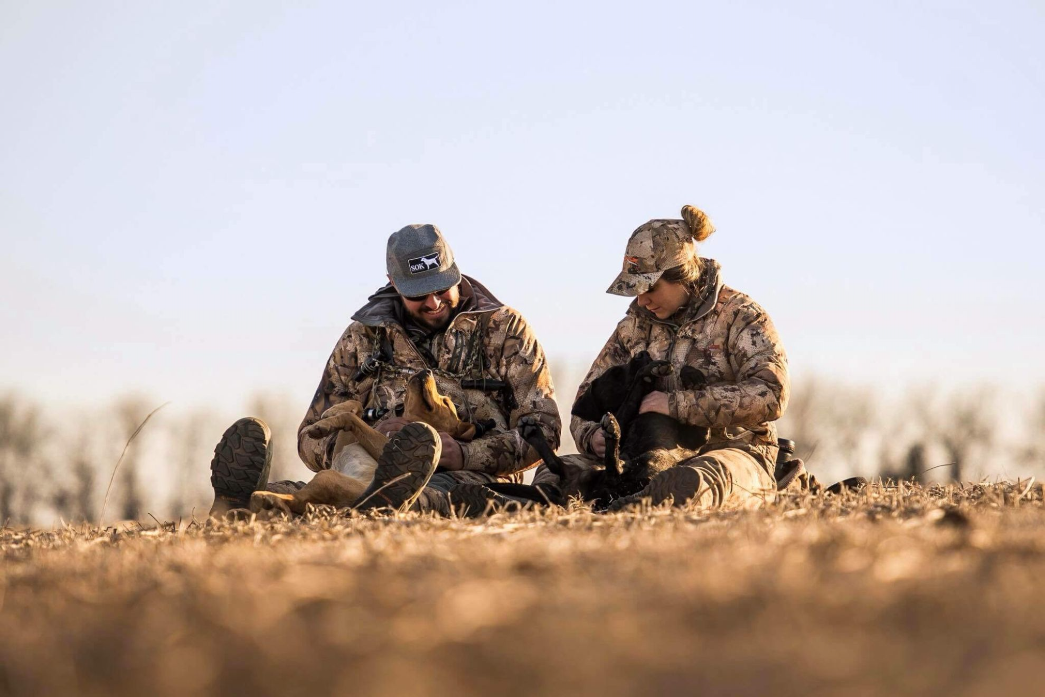 Man and woman taking a break with their Labs during a waterfowl hunt